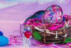 在篮子和玻璃天使的装饰复活节彩蛋与心脏 免版税库存照片
