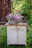在篮子的丁香花束在葡萄酒局在春天庭院里 免版税库存图片