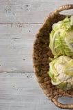 在篮子的两个花椰菜在白色背景 免版税库存图片
