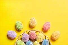 在篮子的五颜六色的复活节彩蛋在黄色背景 免版税库存图片