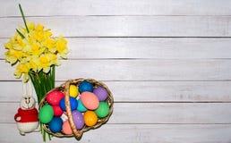 在篮子的五颜六色的复活节彩蛋与水仙和滑稽的兔宝宝可爱的花束在木背景 库存照片