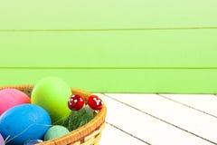 在篮子的五颜六色的复活节彩蛋在木背景 没有暴力的环境友好的材料对动物 免版税库存照片