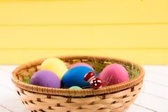 在篮子的五颜六色的复活节彩蛋在木背景 没有暴力的环境友好的材料对动物 库存图片
