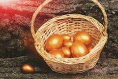 在篮子的传统复活节金黄鸡蛋在木头,古董 免版税库存照片