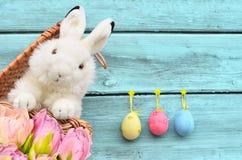 在篮子的兔子用复活节彩蛋和花 免版税库存图片
