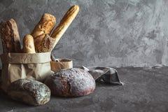 在篮子的可口面包在灰色背景的木桌上 库存图片