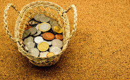 在篮子的国际老硬币在黄柏板 免版税库存图片