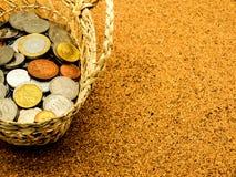 在篮子的国际老硬币在黄柏板 图库摄影