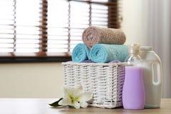 在篮子的在户内桌上的清洁毛巾与百合和洗涤剂 免版税库存图片