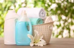 在篮子的在桌上的清洁毛巾与百合和洗涤剂反对被弄脏的背景 免版税库存图片
