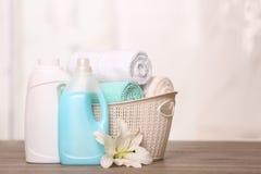 在篮子的在桌上的清洁毛巾与百合和洗涤剂 库存图片