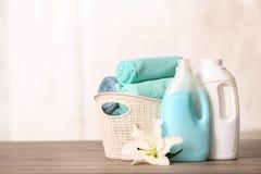 在篮子的在桌上的清洁毛巾与百合和洗涤剂 免版税图库摄影