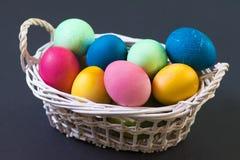 在篮子的复活节多彩多姿的鸡蛋在黑背景 盘旋您色的复活节彩蛋eps10空间文本主题的向量 概念性背景为春天宗教节 免版税库存照片