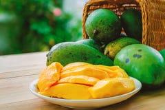 在篮子的成熟芒果果子在木桌上 免版税库存照片