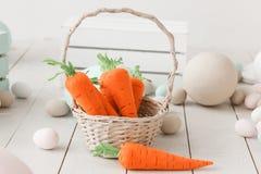 在篮子的手工制造纺织品红萝卜 复活节装饰鸡蛋和兔宝宝 免版税库存照片