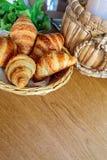 在篮子的新月形面包在木桌上早餐 免版税库存照片