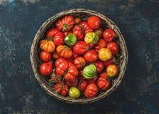 在篮子的新鲜的成熟秋天祖传遗物蕃茄在胶合板背景 库存照片