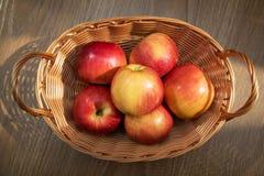 在篮子的新鲜的红色苹果在木背景 库存照片