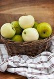在篮子的新鲜的苹果在木桌上 免版税库存照片
