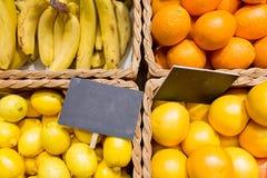 在篮子的果子与标识牌在食物市场上 免版税库存照片