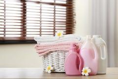 在篮子的清洁毛巾与花和洗涤剂在户内桌上 免版税库存图片