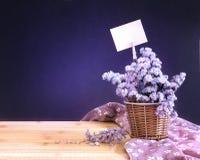 在篮子的甜statice花与在黑暗的bl的白纸标签 免版税图库摄影