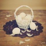 在篮子的白鸡蛋与减速火箭的复活节装饰 库存图片