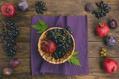 在篮子的秋天果子在木背景 图库摄影
