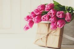 在篮子的紫罗兰色郁金香花束在白色木墙壁前面 免版税库存照片