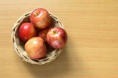在篮子的红色苹果在木背景 图库摄影