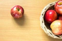 在篮子的红色苹果在木背景 免版税库存图片