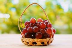 在篮子的红葡萄果子在木桌上 免版税库存图片