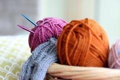 在篮子的编织的纱线球和针 图库摄影