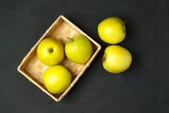 在篮子的苹果在黑暗的木背景 定调子 顶视图 免版税图库摄影