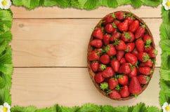 在篮子的草莓在与草莓框架的木桌上离开 免版税库存照片