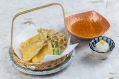 在篮子的鱼和菜天麸罗服务与ponzu与剁碎在washi日文报纸的萝卜 免版税图库摄影