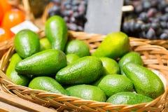 在篮子的鲕梨在食物市场上 库存照片