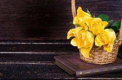 在篮子的黄色玫瑰,在木背景的葡萄酒书 您的文本的空位 库存照片