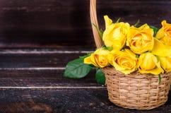 在篮子的黄色玫瑰,在木背景的葡萄酒书 您的文本的空位 免版税库存图片