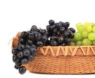 在篮子的黑和绿色葡萄。 免版税库存图片