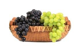 在篮子的黑和绿色葡萄。 库存图片