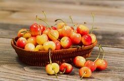 在篮子的水多的金黄更加多雨的樱桃在土气木头 库存照片