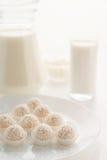 在篮子的Raffaello糖果在一块板材,用在玻璃的牛奶和 免版税图库摄影