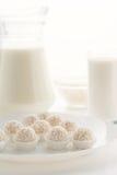 在篮子的Raffaello糖果在一块板材,用在玻璃的牛奶和 图库摄影