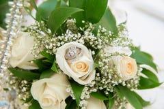 在篮子花束花玫瑰色婚戒的美丽的白色婚礼花束 免版税库存照片