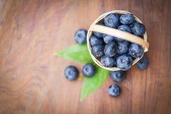 在篮子顶视图蓝莓果子和绿色叶子的新鲜的蓝莓在木桌背景 免版税库存照片
