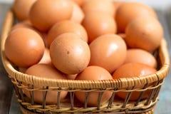 在篮子,关闭的布朗农夫笼子自由的鸡鸡蛋,土气桌 免版税库存照片