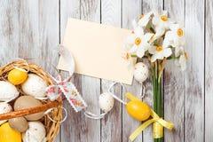 在篮子,空的贺卡,黄水仙花束的复活节彩蛋在木背景的 复活节装饰 免版税库存图片
