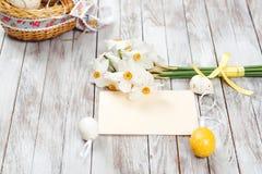 在篮子,空的贺卡,黄水仙花束的复活节彩蛋在木背景的 复活节装饰 免版税库存照片