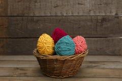 在篮子从毛纱的复活节彩蛋装饰的五颜六色 免版税库存照片